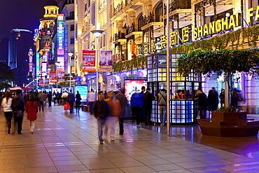 Pedestrians at night walking past stores on Nanjing Road, Shanghai, China, Asia