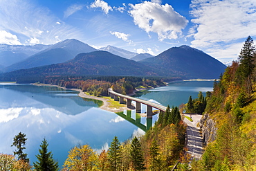 Reflections of a road bridge over Lake Sylvenstein, with mountains in the background, Bavaria, Germany, Europe