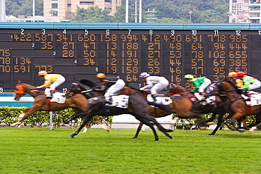 Horses race past large scoreboard during race at Happy Valley racecourse, Hong Kong, China, Asia