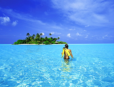 Woman walking with snorkelling equipment to Rihiveli island, Maldives, Indian Ocean, Asia