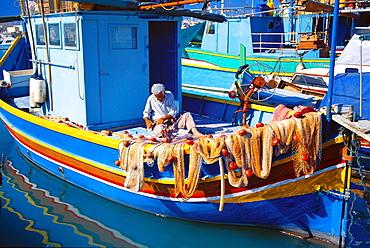 Fisherman knotting a fishing net, Marsaxlokk, Malta, Mediterranean, Europe