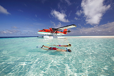 Seaplane and couple snorkeling, Maldives, Indian Ocean, Asia