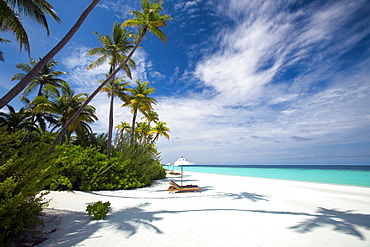 Lounge chairs under shade of umbrella on tropical beach, Maldives, Indian Ocean, Asia