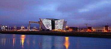 Ireland, North, Belfast, Titanic Quarter, Visitor centre designed by Civic Arts & Eric R Kuhne, illuminated at night.