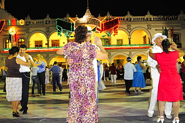 Mexico, Veracruz, Couples dancing in the Zocalo at night illuminated decorations in the national colours for Independence Day celebrations on building facade behind.