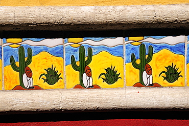 Mexico, Bajio, San Miguel de Allende, Detail of colourful tile depicting figure in Mexican hat sitting at foot of cactus.