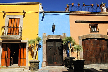 Mexico, Bajio, San Miguel de Allende, Colourful house facades on paved street with plant pots on roof balcony and outside wooden doors.
