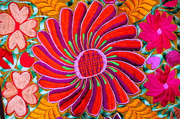 Mexico, Bajio, San Miguel de Allende, Detail of brightly embroidered textile in arts shop with flower design in pink red and orange.