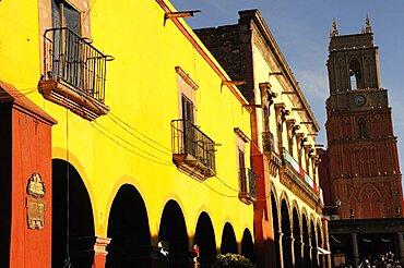 Mexico, Bajio, San Miguel de Allende, El Jardin Yellow facade of colonial mansion and arcades with clock tower beyond.