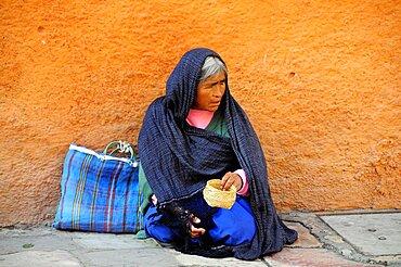 Mexico, Bajio, San Miguel de Allende, Woman begging on street corner.