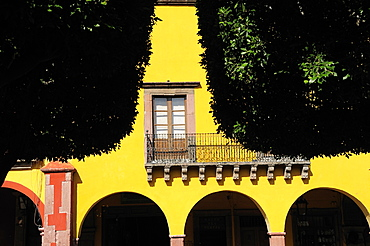 Mexico, Bajio, San Miguel de Allende, El Jardin Detail of yellow painted facade of colonial mansion with French window and balcony part framed by trees in foreground.