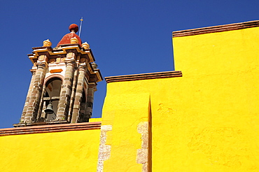 Mexico, Bajio, San Miguel de Allende, Part view of bright yellow exterior wall and church bell tower.