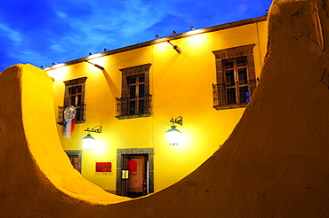 Mexico, Bajio, San Miguel de Allende, Half circle formed wall framing part view of opposite building at night with lighted lamps hanging from brackets at doorway.