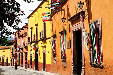 Mexico, Bajio, San Miguel de Allende, Independence Day decorations adorn colonial street lined with brightly painted buildings.