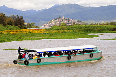 Mexico, Michoacan, Patzcuaro, Crowded passenger boat on Lago Patzcuaro with Isla Janitzio beyond.