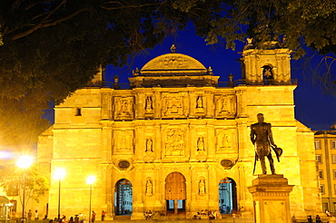 Mexico, Oaxaca, Baroque exterior facade of cathedral at night part framed by tree branches with people and statue in foreground.