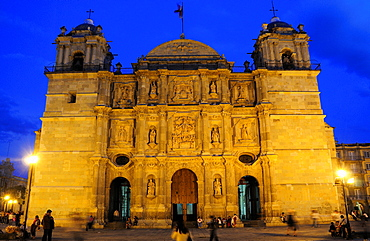 Mexico, Oaxaca, Baroque exterior facade of the Cathedral at night with people in the square in foreground.