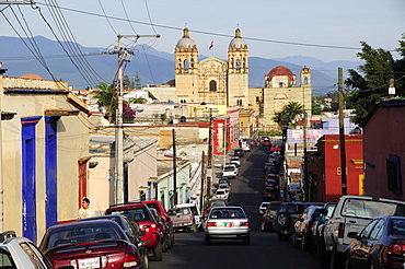 Mexico, Oaxaca, View along street lined by parked vehicles towards church of Santo Domingo.