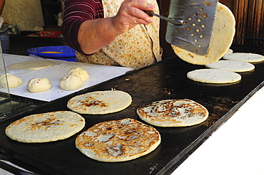 Mexico, Bajio, San Miguel de Allende, Cropped shot of woman making tortillas turning them as they cook on griddle.1