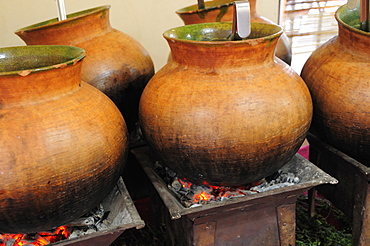 Mexico, Oaxaca, Large earthenware pots of food cooking over hot coals.