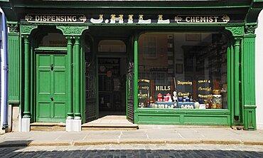 Ireland, County Tyrone, Omagh, Ulster American Folk Park 19th century street Hills chemist shopfront.