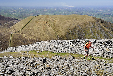 Ireland, County Down, Mourne Mountains, Hiker on Slieve Donard with Slieve Commedagh behind.