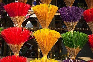 Vietnam, Thuy Zuan Hat village, Colourful bundles of incense sticks for sale.