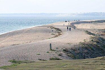 England, Hampshire, Milford on Sea, People walking along Hurst spit a 1.5 mile long shingle ridge.