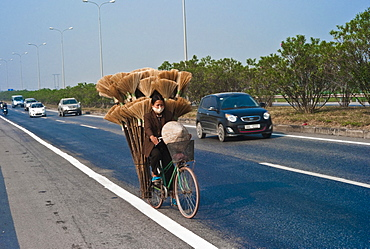 Vietnam, Transport, Woman on Bicycle in north region with a load of brooms.