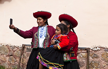 Peru, Chinchero, Young woman in traditional dress using a cell phone to take a picture of herself and other woman with a child.