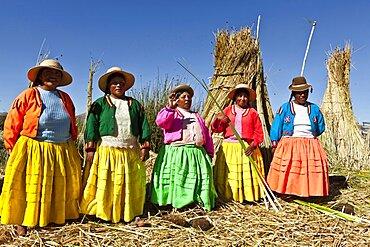 Peru, Puno, Lake Titicaca Women in colorful clothing on Grass Island.