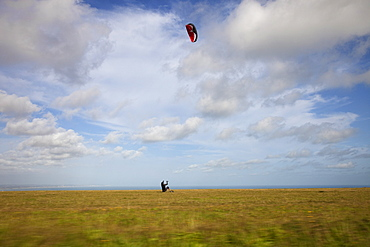 England, East Sussex, Beachy Head, Man Kite Skating along the clifftops shot from moving car.