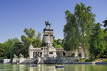 Spain, Madrid, Monument to King Alfonso XII in Parque El Buen Retiro with tourist boating inthe lake.