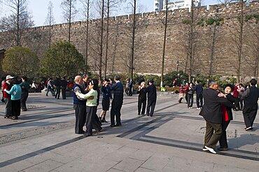 China, Jiangsu, Nanjing, Retired couples enjoying ballroom dancing beneath the old Ming city wall in Xuanwu Lake park with a modern skyscraper in the background.