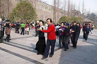 China, Jiangsu, Nanjing, Retired couples dancing beneath the Ming city wall at Xuanwu Lake Park Couples in foreground dancing the tango in a line.