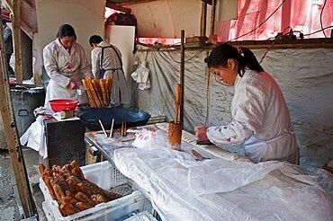 China, Jiangsu, Nanjing, Road-side bakery shop baker cutting strips of dough that will be twisted and deep-fried in a wok to ptoduce Yu Tiao a popular breakfast bread usually eaten with warm soyamilk or porridge or Xi Fan Bundles of Yu Tiao in baskets ready for sale.