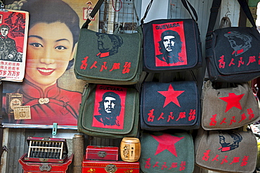 China, Shanghai, Revolutionary kitsch on sale at at Dongtai antique market Chairman Mao Zedong and Che Guevara and Red Star shoulder bags Chinese characters read Serve the People Lin Biao calendar atop Shanghai Belle advertizing poster Fake antique boxes and abacus.