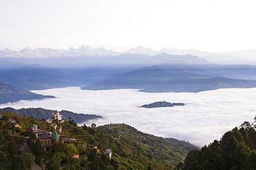 Nepal, Nagarkot, View across clouded valley towards Himalayan mountains.