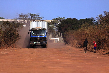Gambia, Transport, Gambia heavy goods vehicle carrying sea container on unsurfaced red dirt road to terminal on the Bund Road.