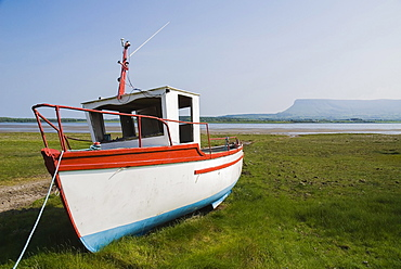 Ireland, County Sligo, Rosses Point, Boat moored on the 3rd beach with Ben Bulben in the background.