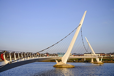 Ireland, North, Derry, The Peace Bridge over the River Foyle opened in 2011 with the former Ebrington Barracks in the background.