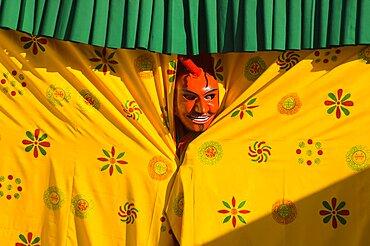 Bhutan, Thimpu Dzong, Atsara, or comedian peering out from behind a curtain at a masked dance Tsecchu.