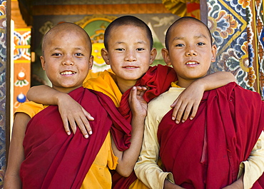 Bhutan, Punakha, Three young novice monks standing in doorway of Chimi Lakhang temple in the old capital.