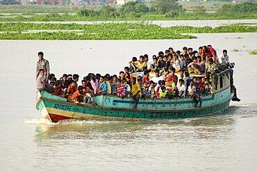 Bangladesh, Dhaka Division, Keraniganj Upazila, Overcrowded boat travelling down a tributary river.,