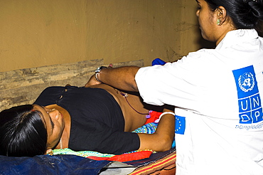 Bangladesh, Chittagong Division, Khagrachari, Pregnant mother being examined by UNDP nurse.