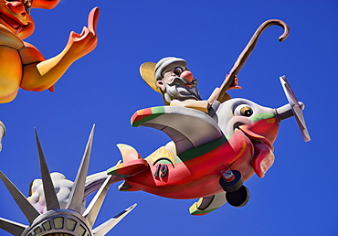 Spain, Valencia Province, Valencia, Papier Mache figure flying an airplane resembling a fish during Las Fallas festival.