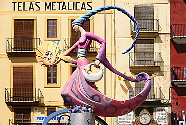 Spain, Valencia Province, Valencia, Papier Mache figure of a lady in a pink dress holding a replica of the sun during Las Fallas festival.