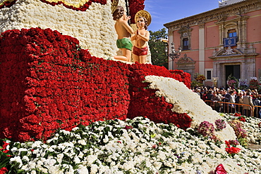 Spain, Valencia Province, Valencia, Base of the Statue of Virgen de los Desamparados, Our Lady of the Forsaken, decked out with flowers carried in the religious procession during Las Fallas festival.