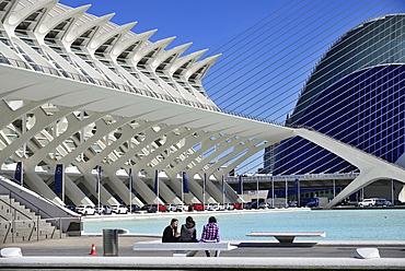 Spain, Valencia Province, Valencia, La Ciudad de las Artes y las Ciencias, City of Arts and Sciences, Principe Felipe Science Museum, General view of the building with girls on seat in the forground and row of Mercedes cars below the building.