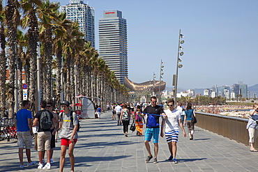 Spain, Catalonia, Barcelona, Barceloneta, Playa de St Sebastia, people walking along the promenade.